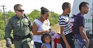 U.S. Border Patrol agents with a group of adult and minor immigrants near Anzalduas Park, southwest of McAllen, Texas. A wave of Central American adults with children and unaccompanied minors has overwhelmed U.S. Immigration and Customs detention centers. (Photo: San Antonio Express-News/ZUMAPRESS.com)