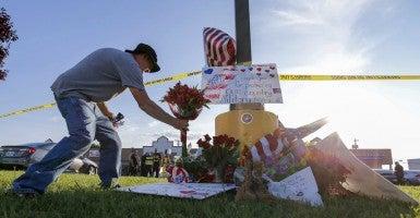 Military veteran David Croft brings flowers to a makeshift memorial for the marines killed in Chattanooga, Tenn. (Photo: Erik S. Lesser/EPA/Newscom)