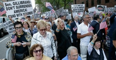 "People hold up signs and wave U.S. flags at a ""Stop Iran Rally"" in New York. The rally was held outside of the office of U.S. Sen. Kirsten Gillibrand, a supporter of President Obama's nuclear deal with Iran. (Photo: Peter Foley/EPA/Newscom)"