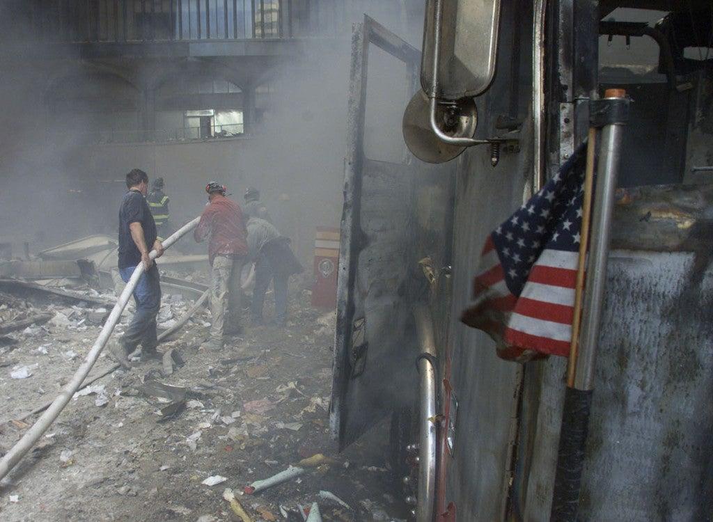 A U.S. flag flies from a burned firetruck near the wreckage. (Photo: REUTERS/Peter Morgan/Newscom)