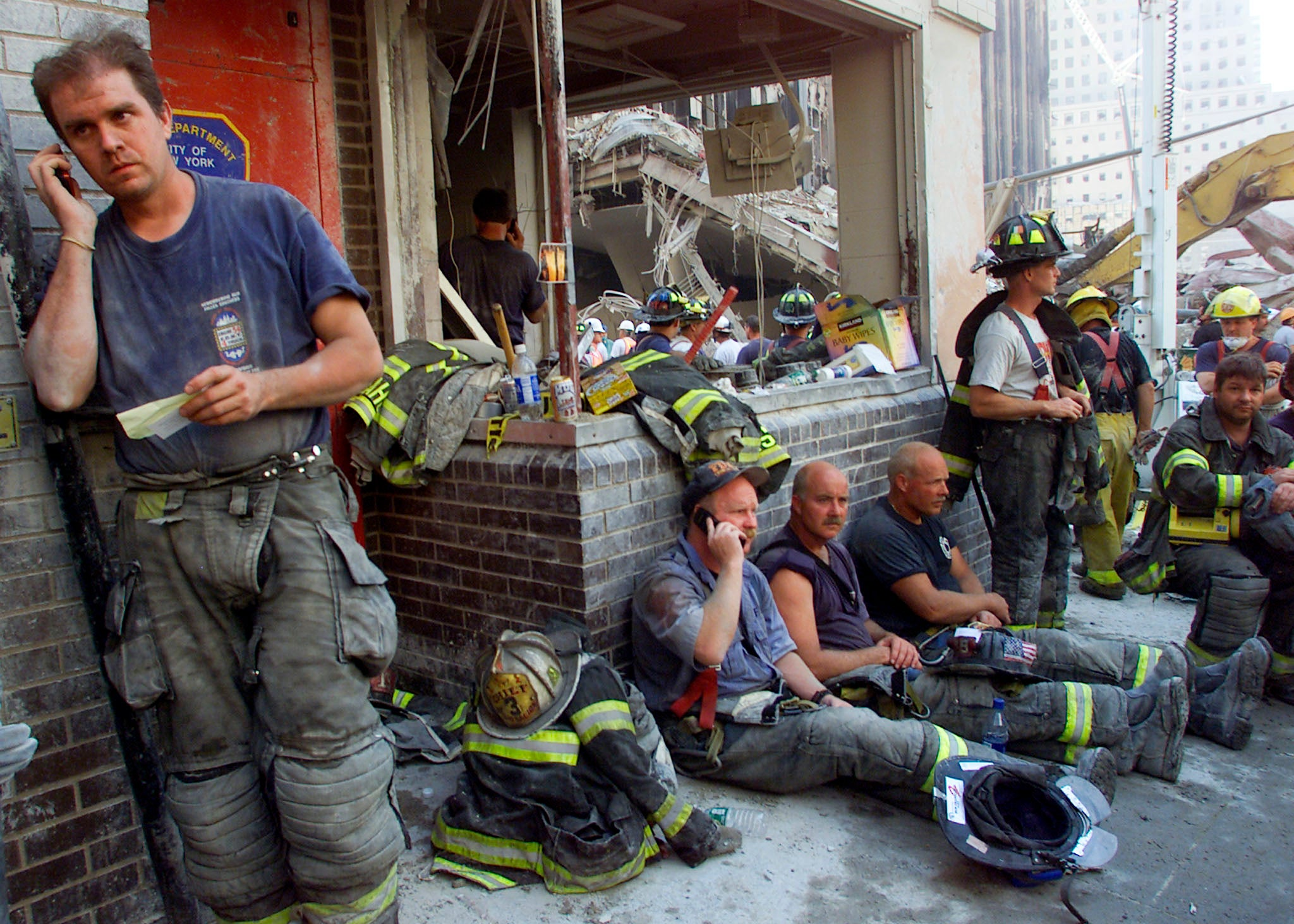 photos of and the days after firemen from around the nation gather at a destroyed firehouse next to the towers as they