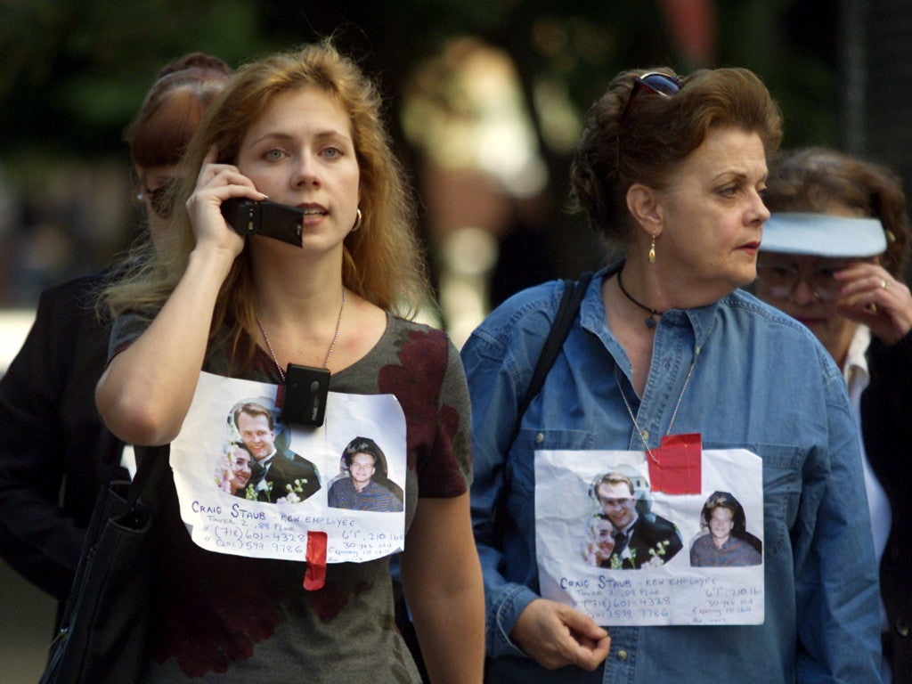 Women wear signs with pictures of missing relatives outside New York's Bellevue Hospital as they wait for word of their fate. (Photo: REUTERS/Shaun Best/Newscom)