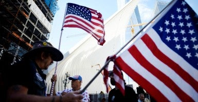 Men holding American flags stand near the National September 11 Memorial during memorial observances on the 14th anniversary of the 9/11 terror attacks in New York, New York, USA, 11 September 2015. (Photo: Justin Lane/EPA/Newscom)