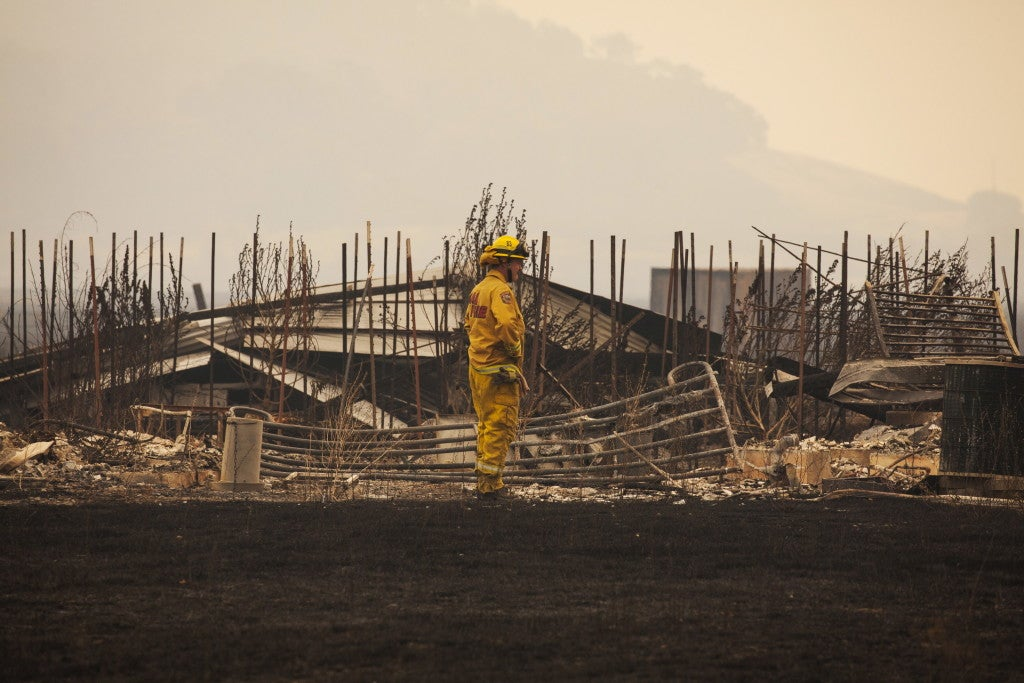 """A firefighter surveys a destroyed home at the """"Valley Fire"""" near Middleton, California, September 14, 2015. Fire officials saying they expect the property toll to climb. (Photo: REUTERS/David Ryder/Newscom)"""