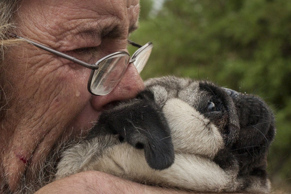 Hooper hugs his dog Toby on his property after seeing the damage of the northern California fire that's claimed one life and burned at least 400 homes to the ground. (Photo: REUTERS/David Ryder/Newscom)