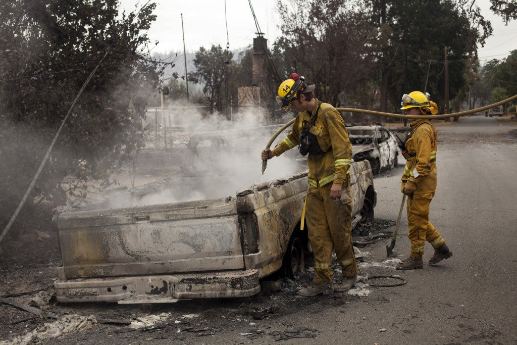 Firefighters extinguish a flare up in an automobile burnt by the Valley Fire near Middletown, California, September 14, 2015.  (Photo: REUTERS/David Ryder/Newscom)