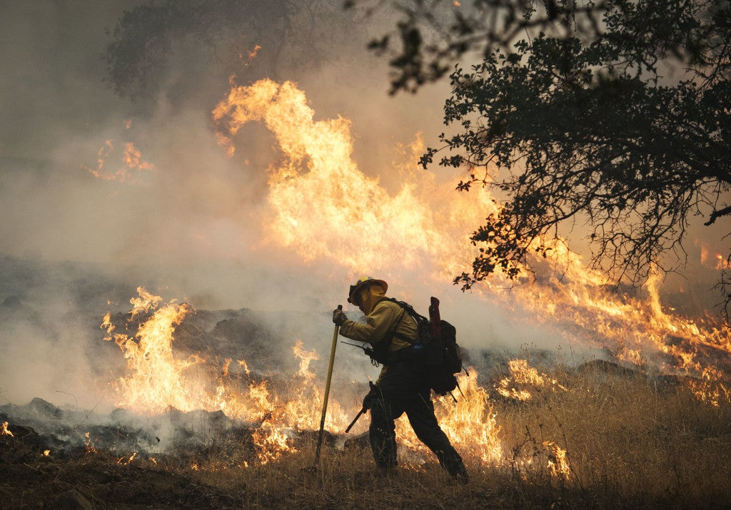 A firefighter lights a back burn along Highway 29 north of Middletown in Lake County, Calif. (Photo: Randy Pench/Newscom)