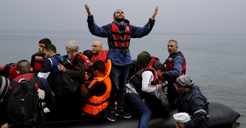 A Syrian refugee gives thanks to God as he arrives in an overcrowded dinghy on the Greek island of Lesbos after crossing part of the Aegean Sea from Turkey. (Photo: Yannis Behrakis/Reuters/Newscom)