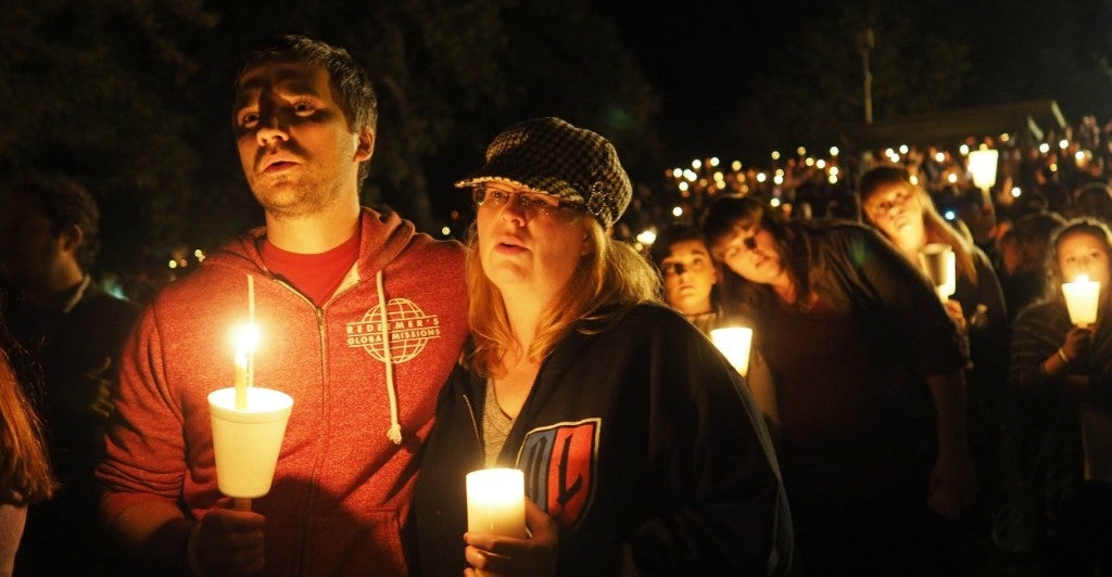 Pastor Grant Goins and Rosemary Alwan sing along to 'Amazing Grace' during a candlelight vigil, held Thursday, October 1, 2015 in Roseburg, Oregon, for the victims of the mass shooting. (Photo: Amiran White/ZUMA Press/Newscom)