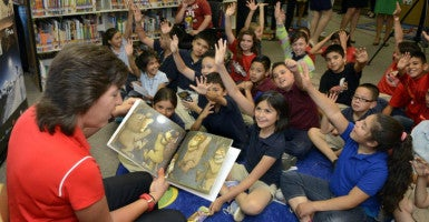Yvonne Sanchez, New Mexico University women's basketball coach, reads ''Where the Wild Things Are'' to third- and fourth- graders May 13 at Kit Carson Elementary School in Albuquerque, N.M. (Photo: Greg Sorber/Zuma Press/Newscom)