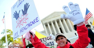 A protester demonstrates in front of the U.S. Supreme Court as the court hears its third day of arguments on the constitutionality of President Barack Obama's health care bill in Washington, D.C., on March 28, 2012. (Photo: Kevin Dietsch/UPI/Newscom)