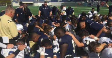 Players from Cambridge Christian School and University Christian School pray midfield before their state championship game. (Photo courtesy Tim Euler)