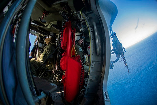 An MH-60S air crewman with Helicopter Sea Combat Squadron 28, Iwo Jima Amphibious Ready Group, gazes out of the gunner's door of a Seahawk helicopter while participating in flight operations over the Atlantic Ocean. (Photo: Cpl. Todd F. Michalek/Released)