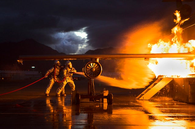 Marines with Aircraft Rescue and Fire Fighting douse flames engulfing a mobile aircraft firefighting training device as a part of night time 360 degree firefighter training aboard Marine Corps Air Station Kaneohe Bay. (Photo: Cpl. Matthew Callahan/Released)