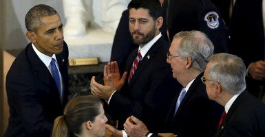 President Obama shakes hands with Senate Majority Leader Mitch McConnell  during a Dec. 9 event on Capitol Hill. Flanking McConnell are House Speaker Paul Ryan and Senate Minority Leader Harry Reid.  (Photo: Gary Cameron/ Reuters/Newscom)