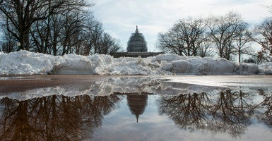 The U.S. Capitol building reflects in a pool of water from the melting snow a recent snowstorm dumped nearly two feet of snow in Washington. (Photo: Bill Clark/CQ Roll Call/Newscom)