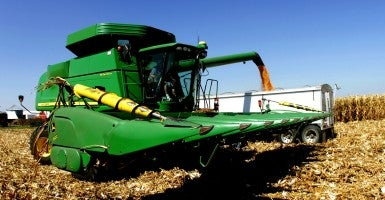 A farmer transfers corn from his combine to a grain truck at his farm in Iowa. (Photo: Larry Fisher/ZUMA Press/Newscom)