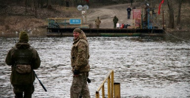 Ukrainian soldiers at the ferry crossing in Lobacheve keep an eye on separatist troops on the opposite shore. (Photo: Nolan Peterson/The Daily Signal)