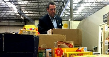 Rep. Mark Walker, R-N.C., helps sort inventory for a food pantry in Greensboro, N.C.  (Photo: Philip  Wegmann/ The Daily Signal)