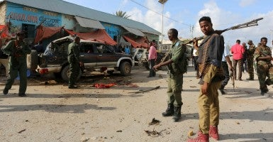 Somali policemen gather near the wreckage of a car at the scene of an explosion following an attack in Somalia's capital Mogadishu, March 9. (Photo: Feisal Omar/Reuters/Newscom)