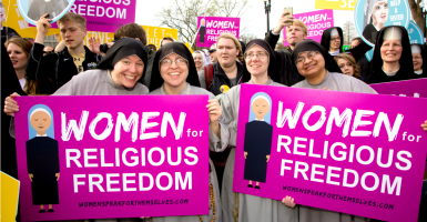 Catholic nuns holding signs in front of the Supreme Court building. (Photo: Jeff Malet Photography/Newscom)