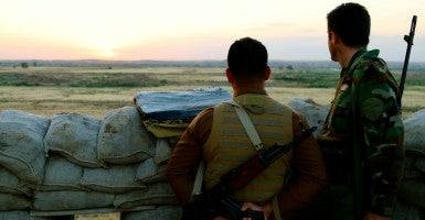 Kurdish soldiers look toward ISIS lines. (Photo: Nolan Peterson/The Daily Signal)