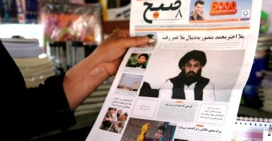 An Afghan man reads the news of Taliban leader's death on a local newspaper in Kabul, Afghanistan. (Photo: Rahmat Alizadah)