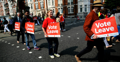 Supporter holding banners cross the road during a Vote Leave event. (Photo: Neil Hall/Reuters/Newscom)