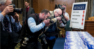 Photographers snap pictures of President Barack Obama's budget proposal. But so far, Congress has failed to agree to any budget. Now some conservatives call on lawmakers to skip one altogether. (Photo: Bill Clark/CQ Roll Call/Newscom)