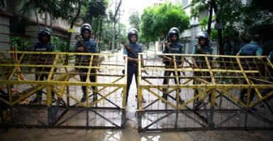Security officials stand guard behind barbed wire barricade at a checkpoint in the streets close to the Holey Artisan Bakery, site of a terrorist attack in Dhaka, Bangladesh. (Photo: STR/EPA/Newscom)