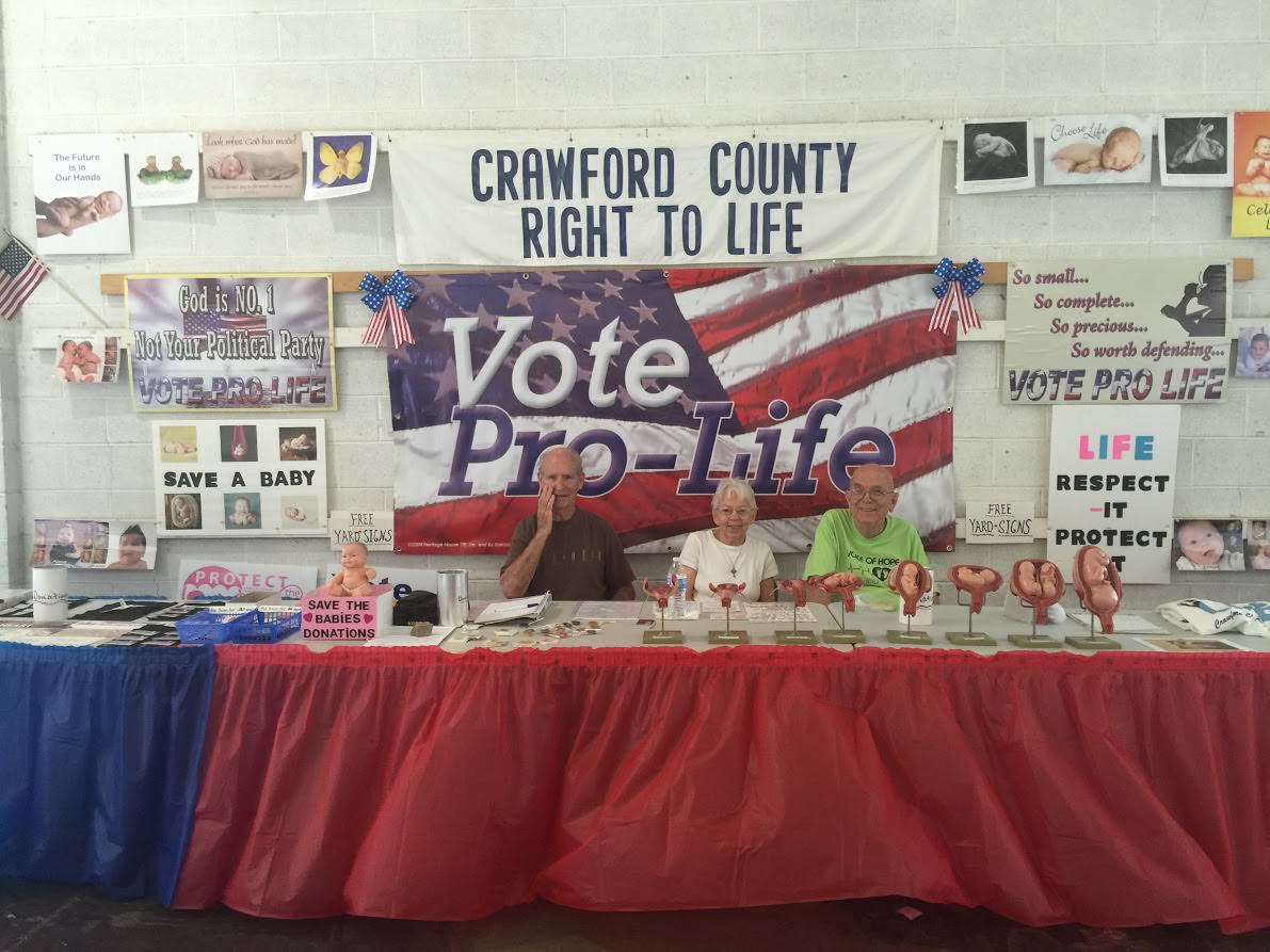 Dick and Dolly Hatfield (left) and Gary Bishop (right) sit at a booth for Crawford County Right to Life at the Crawford County Fair. (Photo: Rob Bluey/The Daily Signal)