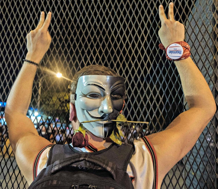 A protester flashes the peace sign to police officers across a barrier fence at the Democratic National Convention. (Photo: Christopher Occhicone/ZumaPress/Newscom)