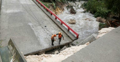 Members of the Guatemalan emergency commission stand on a bridge that collapsed after heavy rains brought by Hurricane Earl at Melchor de Mencos, Guatemala, Aug. 4, 2016. Hurricane Earl serves as an important reminder for Congress to rethink disaster management. (Photo: Stringer/Reuters /Newscom)