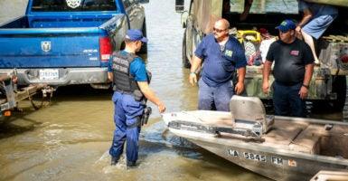 U.S. Coast Guard Chief Petty Officer Jonathan Tarroe coordinates with members of a local fire department and other local officials helping evacuate area citizens, Baton Rouge, Louisiana, Aug. 16, 2016. (Photo: PO2 LaNola Stone/UPI /Newscom)