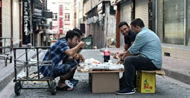 These men pictured Aug. 20, 2016, are among about 300,000 Syrian refugees  living in Istanbul, Turkey. One study found it costs 12 times more to resettle refugees here rather than their home region. (Photo: Raddad Jebarah /Zuma Press/Newscom)
