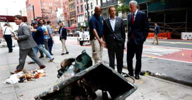 New York Mayor Bill de Blasio and New York Gov. Andrew Cuomo look over a mangled dumpster while touring the site of an explosion that occurred overnight in New York City. Over 20 people were injured in the blast. (Photo: Justin Lane/EPA/ Newscom)