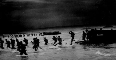 """From Coast Guard-manned 'sea-horse' landing craft, American troops leap forward to storm a North African beach during final amphibious maneuvers."" James D. Rose, Jr., 1944."