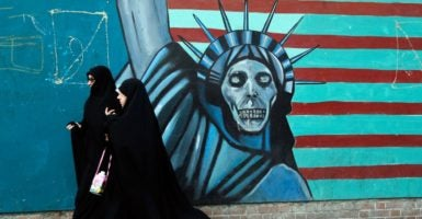 Iranian women pass next to an anti-U.S. mural on their way to the former U.S. Embassy in Tehran.(Photo: Abedin Taherkenareh/EPA/Newscom)