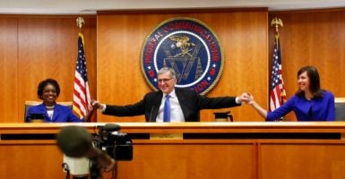 Federal Communications Commission Chairman Tom Wheeler, middle, clasps hands in victory with his two Democratic colleagues on the commission, Jessica Rosenworcel and Mignon Clybern, after voting in favor of a net neutrality measure on Feb. 26. (Photo: Yuri Gripas/Reuters /Newscom)