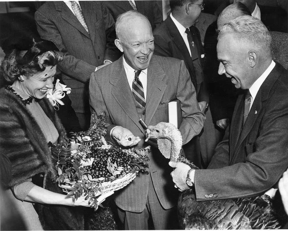 President Dwight D. Eisenhower receives a 43-pound turkey from Perry Browning of Winchester, Ky., president of the National Turkey Federation. Eisenhower holds the book, 'Turkey Management,' which was also presented. (Photo: Archives/Eisenhower Presidential Library)