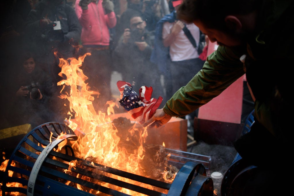 Protesters burn an American flag in Washington, D.C., following the inauguration of President Donald Trump. (Photo: Monica Jorge/Sipa USA/Newscom)