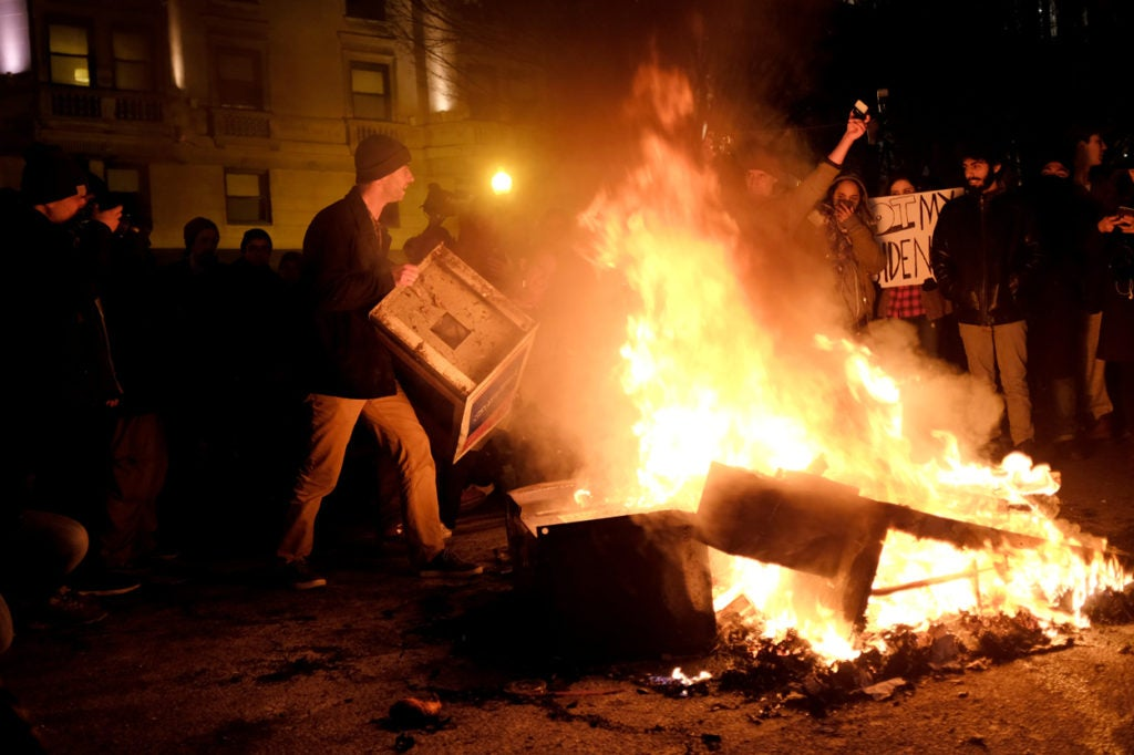 Protesters burn trash and newspaper dispensers in the road outside the offices of The Washington Post. (Photo: James Lawler Duggan/Reuters/Newscom)