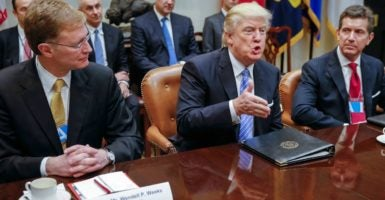 President Donald Trump, Corning CEO Wendell Weeks, and Johnson & Johnson CEO Alex Gorsky attend a meeting with business leaders in the White House. (Photo: Shawn Thew/EPA/Newscom)