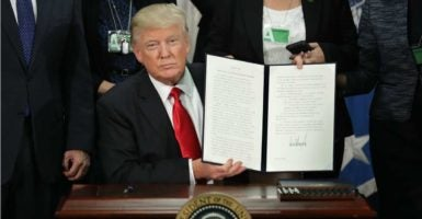 President Donald Trump, at the Department of Homeland Security, shows one of the two executive orders he signed Wednesday tackling illegal immigration. (Photo: Chip Somodevilla/CNP/AdMedia/Newscom)