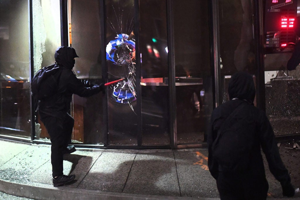 A rioter smashes a window at a Mechanics Bank branch in Berkeley, California. (Photo: Noah Berger/EPA/Newscom)
