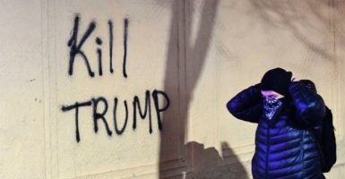 A woman passes graffiti written by protesters who held a demonstration against Breitbart News editor Milo Yiannopoulos in Berkeley, California. (Photo: Noah Berger/EPA/Newscom)