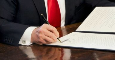 President Donald Trump signs an executive order to review financial regulations of the Obama administration era. (Photo: Aude Guerrucci/CNP /AdMedia/Newscom)