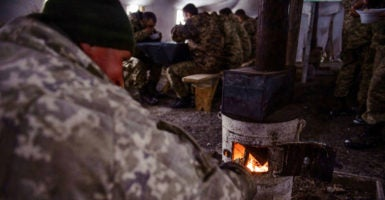 Ukrainian soldiers keep warm during a meal in Volnovakha. (Photo: Olga Ivashchenko)