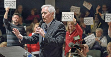 Rep. Tom McClintock, R-Calif., is interrupted as he tries to field questions Feb. 4 from an audience of about 150 in Roseville, California. Anti-Trump  demonstrators chanted slogans, carried signs, and blocked traffic outside. (Photo: Randall Benton/Zuma Press/Newscom)
