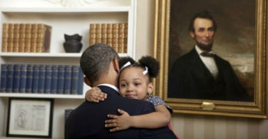 In front of a portrait of Abraham Lincoln, President Barack Obama holds 3-year-old Arianna Holmes  before taking a photo with her family Feb. 1, 2012, in the Oval Office. (Photo: Lawrence Jackson/Zuma Press/Newscom)